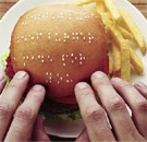 Blind person touching a Braille hamburger bun at McDonald's
