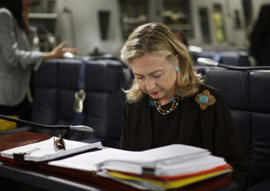 Clinton sighing at a desk