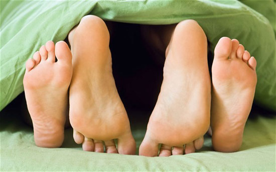 A couple's feet at the foot of the bed