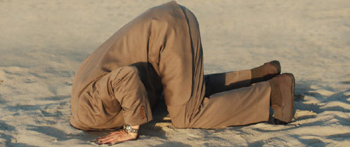 Man with his head in the sand crying