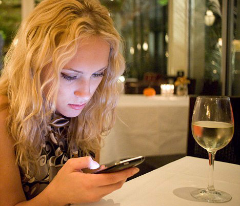 Girl texting on her phone during a first date at a restaurant table