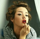 Hot girl putting on red lipstick
