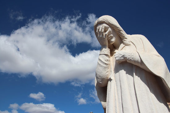 Statue of Jesus weeping with sky in background