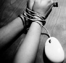 Mouse cord tied around girl's wrists