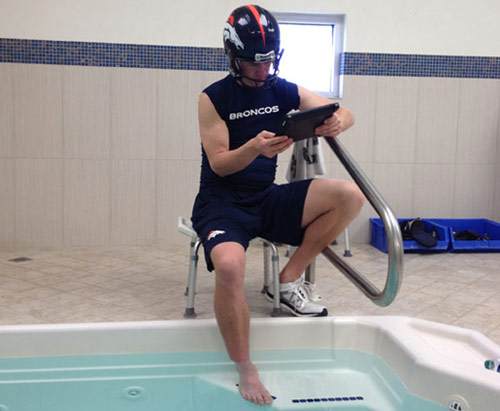 Peyton Manning putting his foot in a pool with helmet on