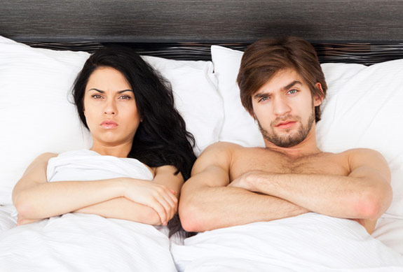 Man and woman sitting in bed about to sign a sexual consent contract