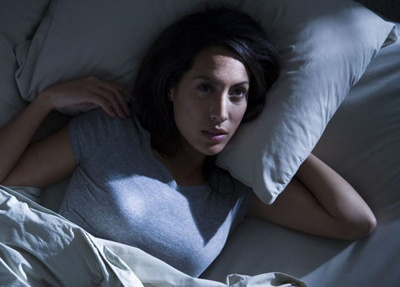 Woman lying in bed can't fall asleep with her eyes open