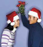 Guy holding mistletoe branch over a girl in a Santa hat