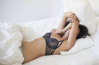 Woman in a bra laying on the bed in a sexy pose