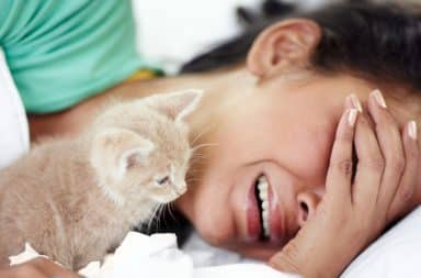 Woman crying herself to sleep in bed with a kitten
