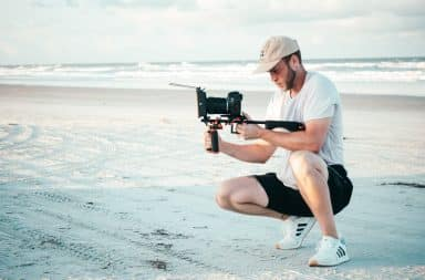 Man filming on the beach