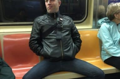 Man is manspreading on the subway taking up three seats