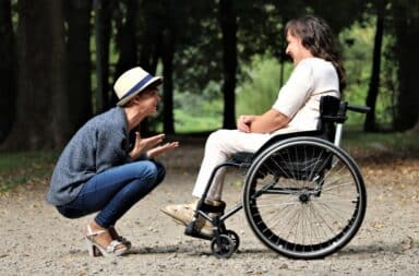 Two women outside, one in a wheelchair