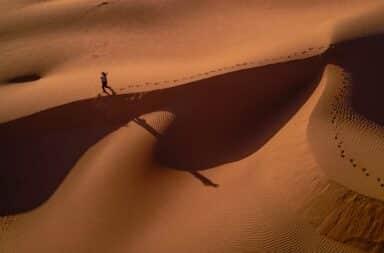 Man walking alone in Sahara Desert