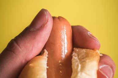 Person holding a hot dog peeking out of a bun