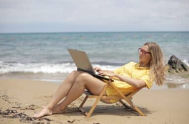 Woman typing at a laptop on the beach in a chair
