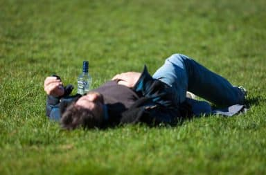 Man laying in the grass hungover with a bottle of Smirnoff vodka liquor