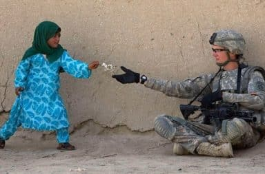 Middleeastern child handing a US soldier a gift