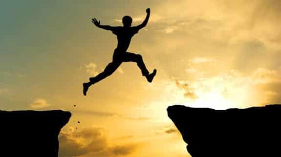 Man jumping across cliffs