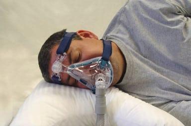 Man wearing sleep apnea mask in bed
