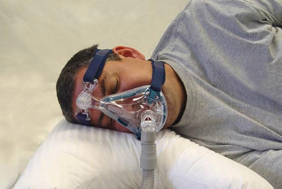 Man wearing sleep apnea mask in bed