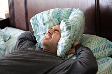 Man holding a pillow over his ears because of loud, annoying neighbor