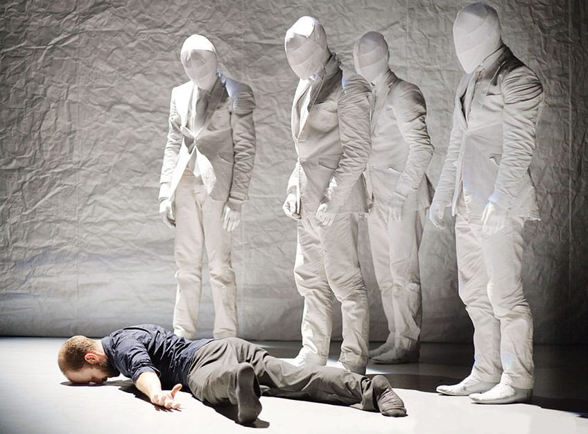 Man lying on ground next to five corporate mummies