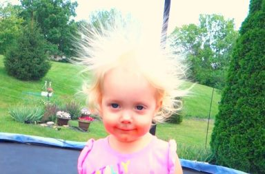 Toddler on a trampoline has crazy blonde hair standing up