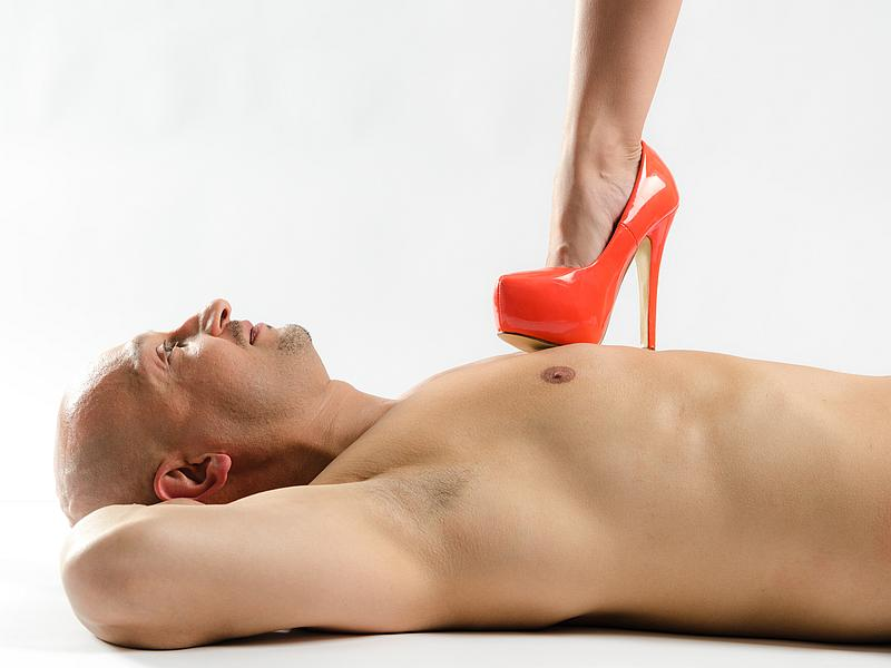 Woman standing on a man's chest with her red high heel