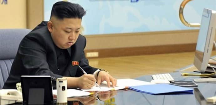 Kim Jong Un writing at a table