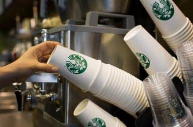 Starbucks employee grabbing cups