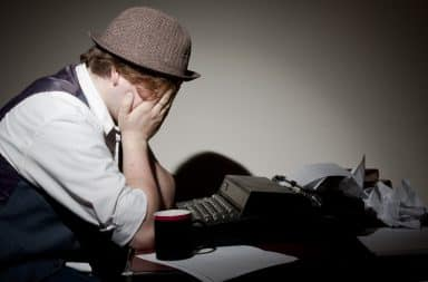 Man with hands on his face at a typewriter