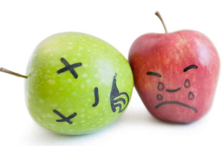 Apples with faces drawn on them in black marker
