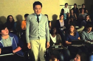Man standing up in college classroom being stared at