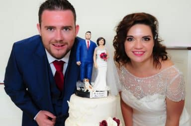 Couple next to a wedding cake with themselves on it