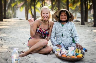 Woman backpacking Asia sitting on the beach with older woman