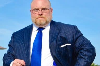 Balding, overweight man in a suit and tie