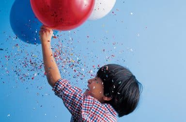 Boy holding a balloon with confetti raining down