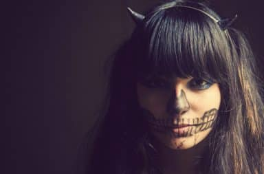 Woman with black makeup and devil horns