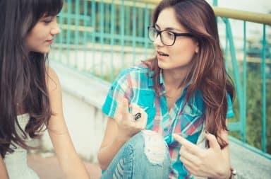 Hipster girls talking on the sidewalk