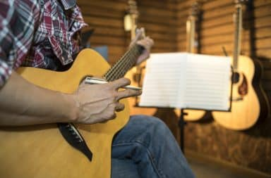 Man playing a guitar and writing a song