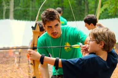 Boy shooting an arrow in the woods at camp