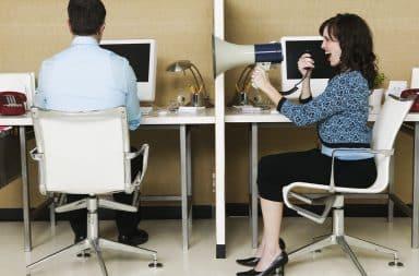 Woman yelling at man using a bullhorn at work desks