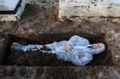 Dead Jewish man lying in an open grave at a cemetery