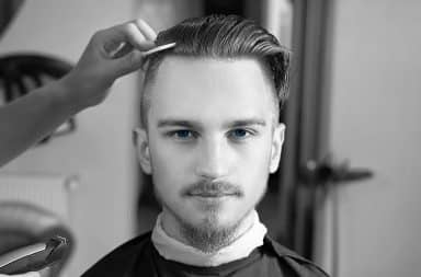 Black and white photo of a man with an undercut haircut and blue eyes