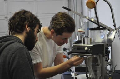 Coffee machine inspection by two men