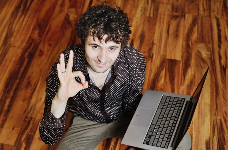 Man holding a laptop and the OK sign with his hand