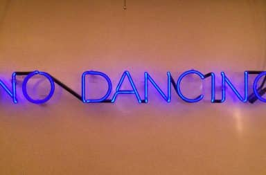 "Neon purple ""no dancing"" sign"
