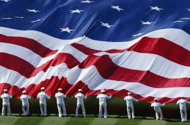 Marines holding a large American flag and waving it