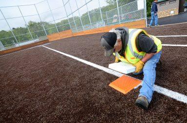 Man doing maintenance on third base